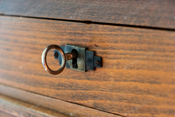 Secret, mystery concept. Close up view of a retro key on an old fashioned keyhole