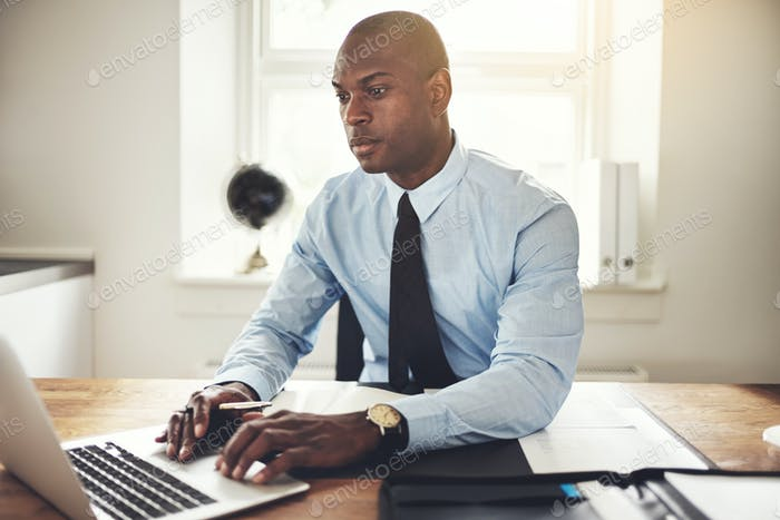 Young businessman working on a laptop in an office