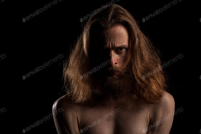 Hipster with long hair and beard on black background