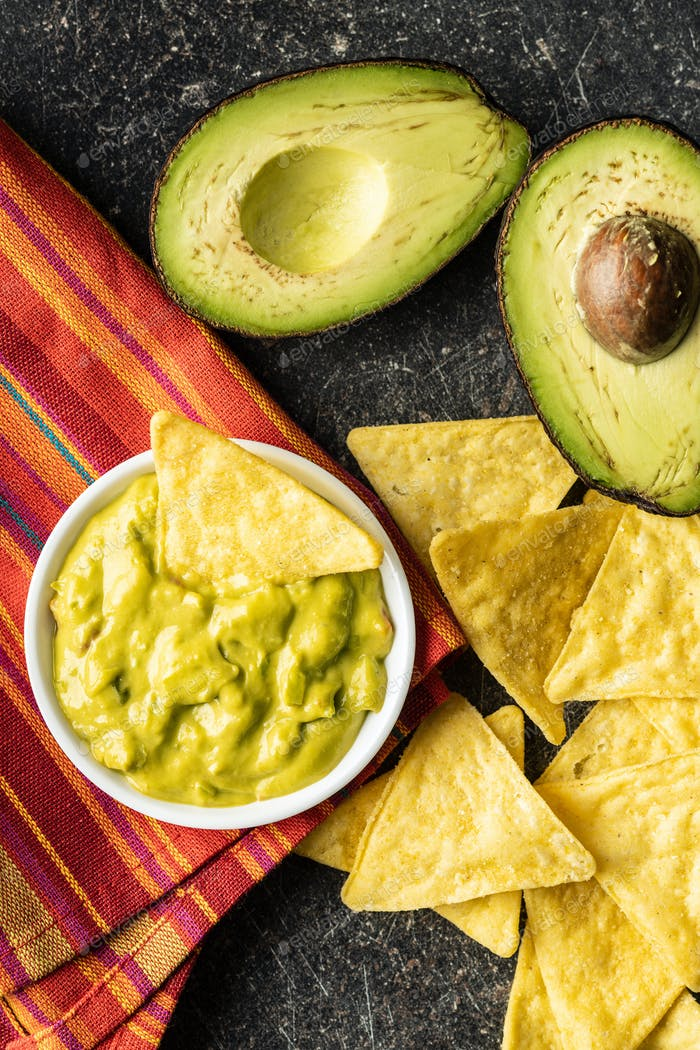 Corn nacho chips and avocado dip. Yellow tortilla chips and guacamole