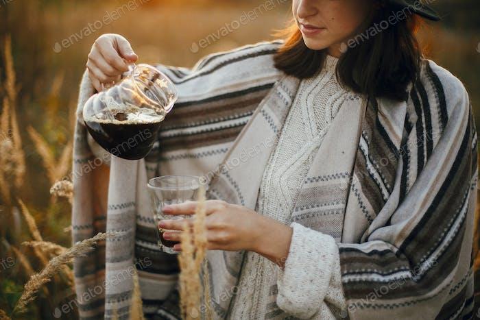 Mujer Hipster en sombrero verter café caliente fresco en taza de vidrio