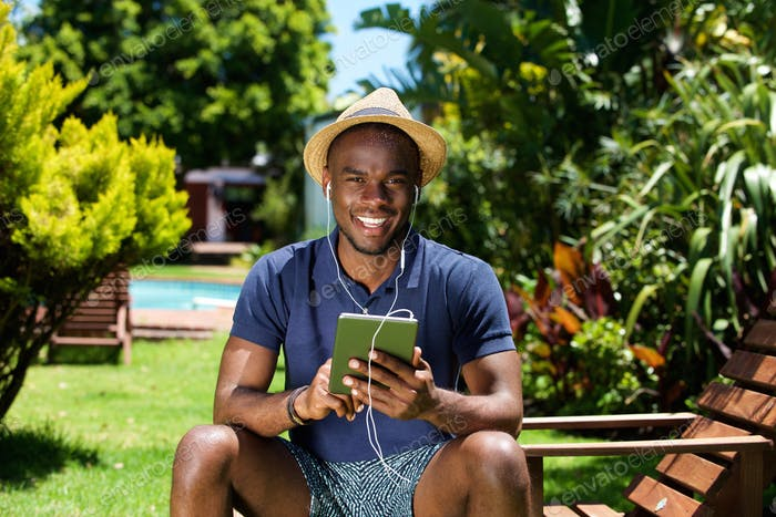 Happy young man listening to music on digital tablet