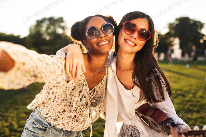Two beautiful girls in sunglasses friendly hugging each other wh