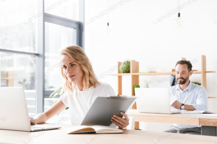 Focused woman manager working on laptop computer
