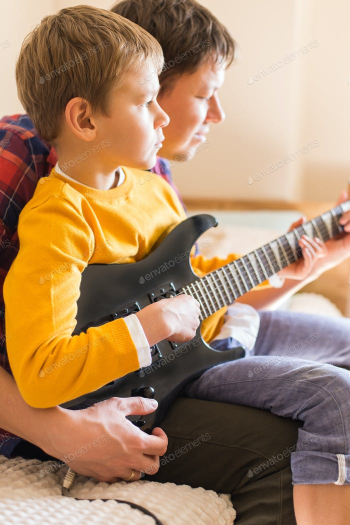 Millennial father and son playing, practicing electric guitar at home