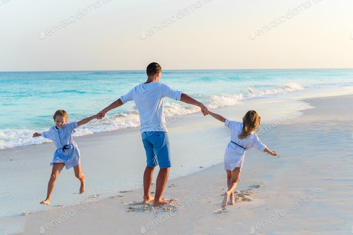 Family walking on white beach on caribbean island in the evening