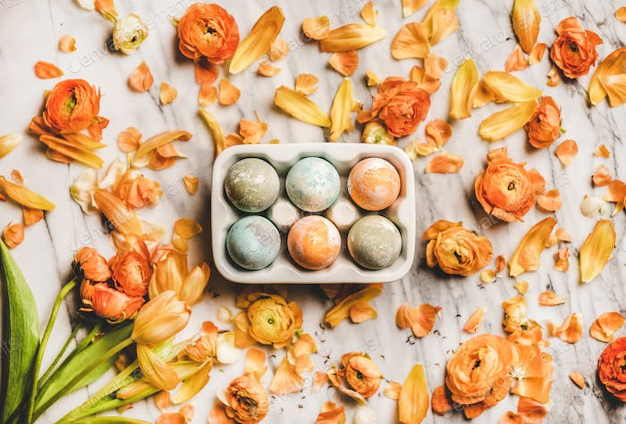 Colorful dyed Easter eggs over blossom orange flowers on marble