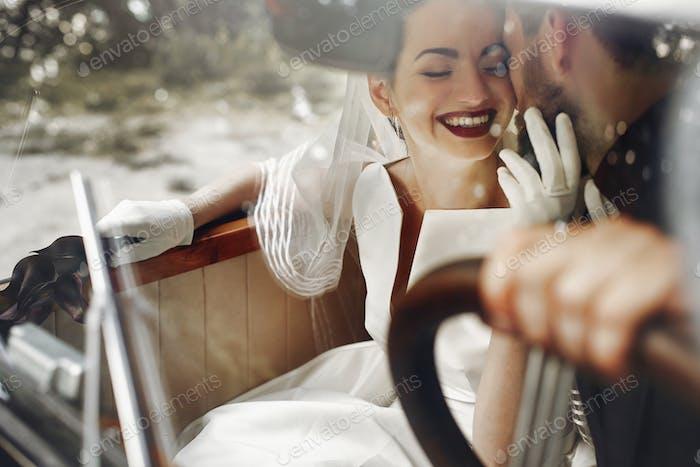 Wedding couple posing in stylish black car