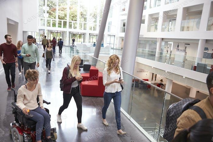 Los estudiantes caminan y hablan Uso dispositivos Móvil en la universidad