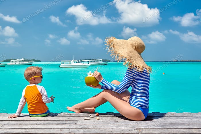 Toddler boy with mother sitting on wooden jetty