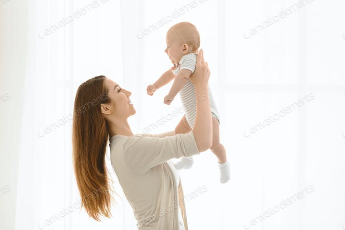 Young woman lifting her adorable newborn baby up in air