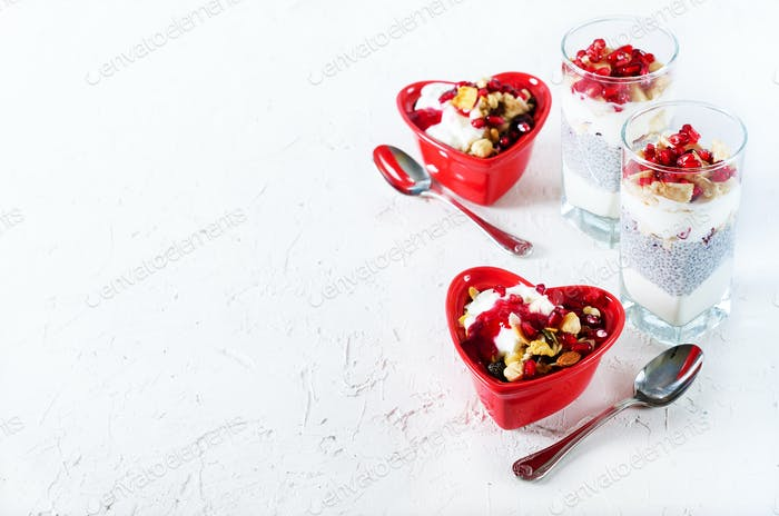 Homemade granola with yogurt in red heart plate on white table. Romantic breakfast. Free space for