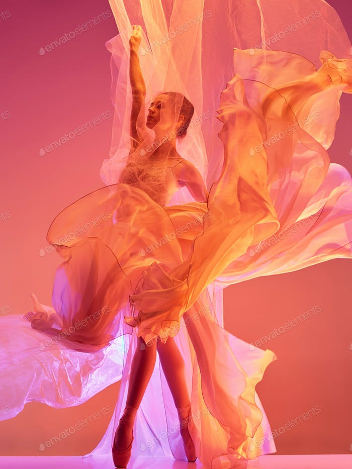 Ballerina. Young graceful female ballet dancer dancing over red studio. Beauty of classic ballet.