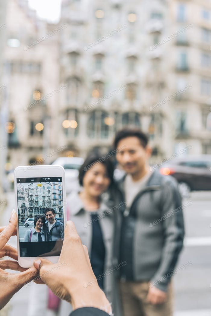 Asian tourist couple taking a picture with a mobile phone