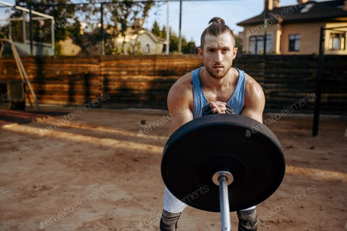 Man prepares barbell weights, street workout