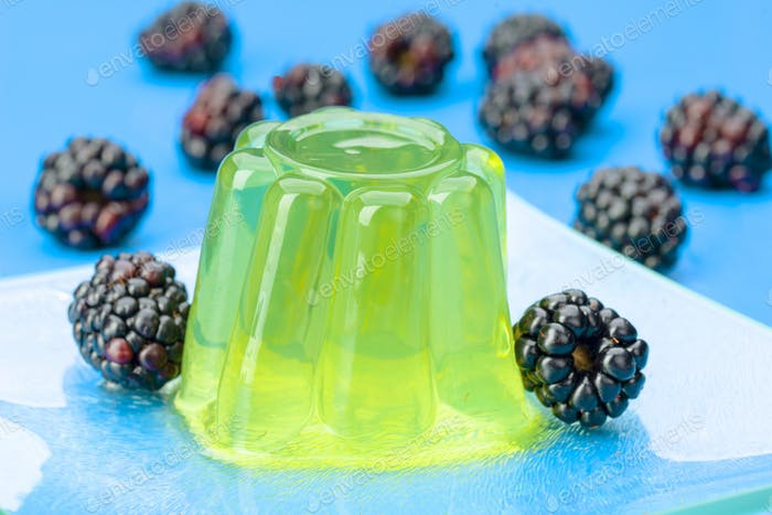 colored gelatin and blackberries on blue background