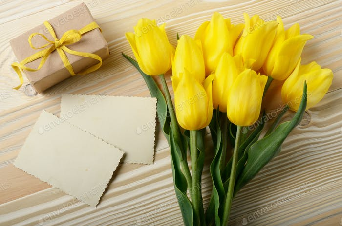 Yellow tulips near blank greeting card and gift box on natural w