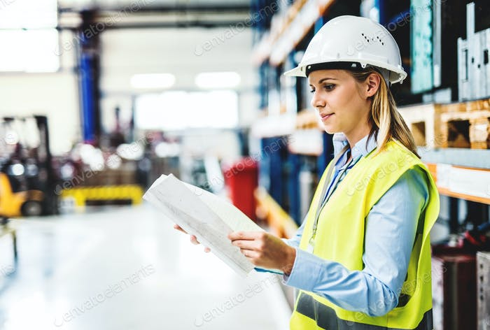 A portrait of an industrial woman engineer in a factory holding paperwork.