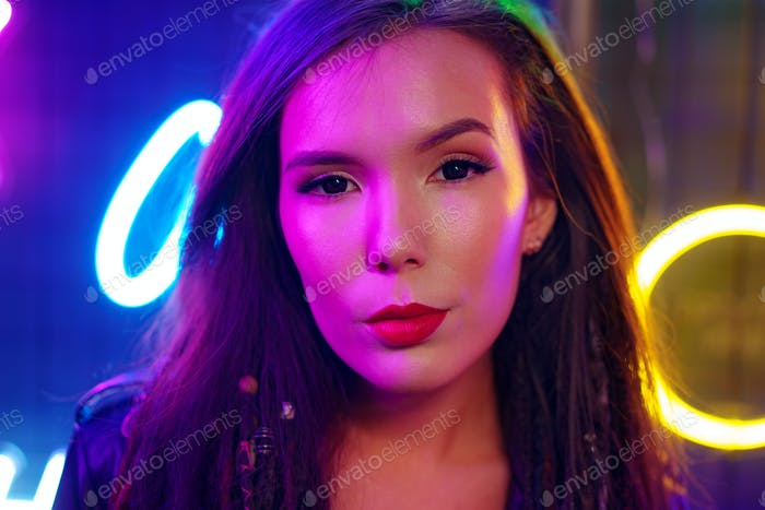 Portrait of a young attractive female standing near neon lamps at night