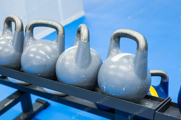 Blue kettlebells in a row in a gym - focus on the front kettlebell