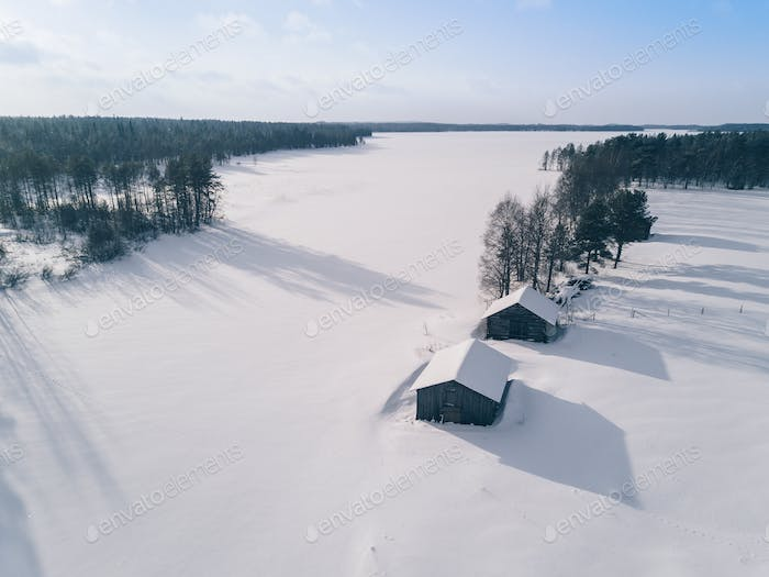 Aerial view over snowy lake and winter forest