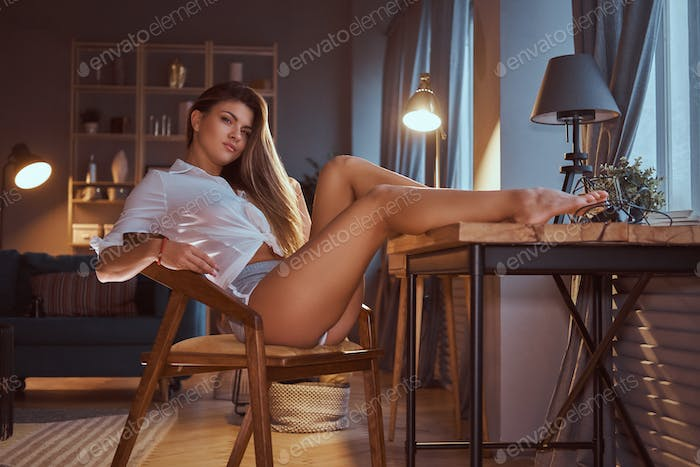 Sexy girl in a translucent blouse sits on a chair with her legs on the table at home