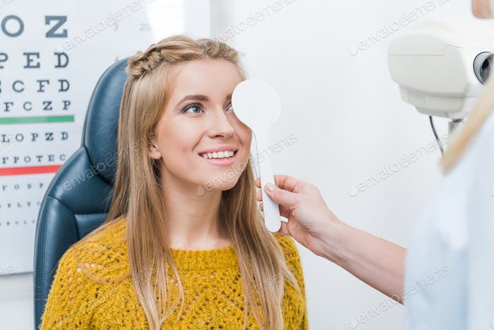oculist examining beautiful young patient in clinic