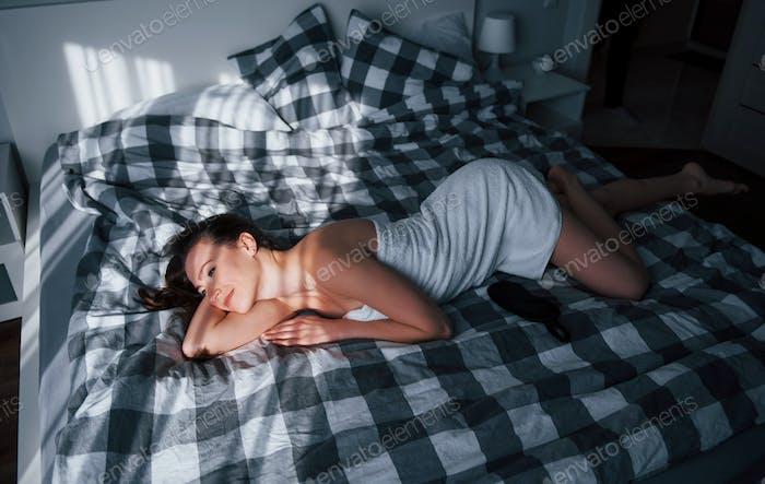Ruhen und Wohlfühlen. Hübsche junge Frau liegt morgens auf dem Bett in ihrem Zimmer