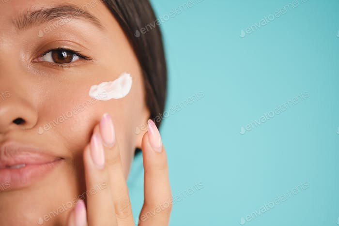 Close up pretty Asian girl applying cream on clean skin over colorful background