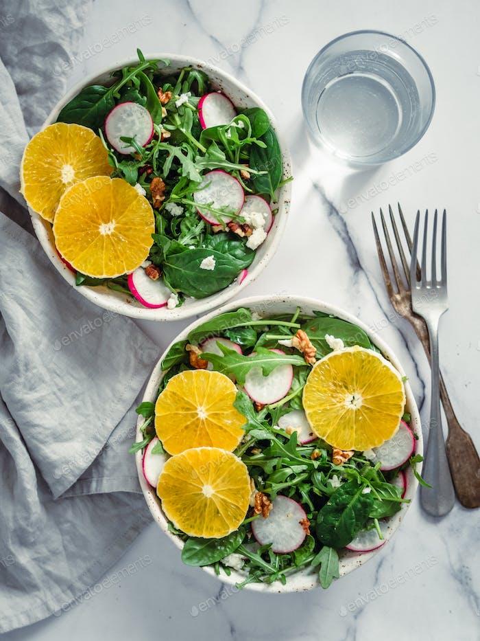 Salad bowl with oranges, spinach, arugula, radish
