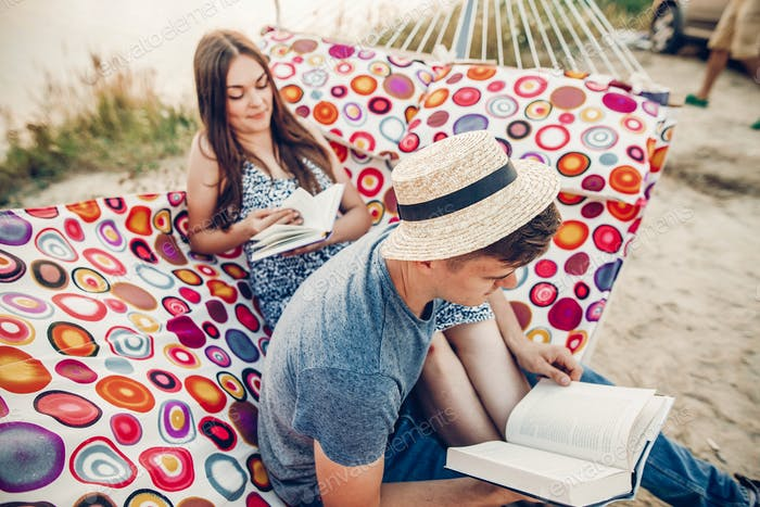 Happy hipster couple reading books and relaxing in hammock in sunset light