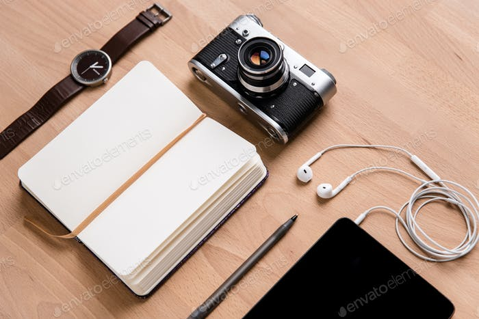 Notepad, tablet, earphones, camera watch and pen on wooden table