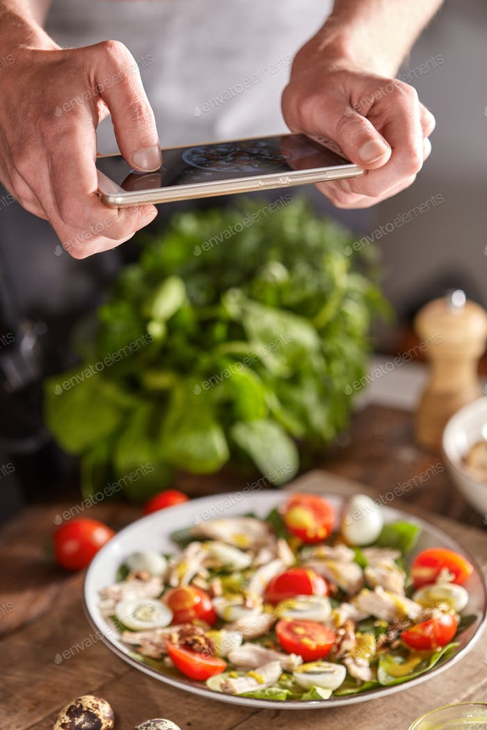 The photo of healthy salad by mobile smartphone, make a cooker above a wooden table