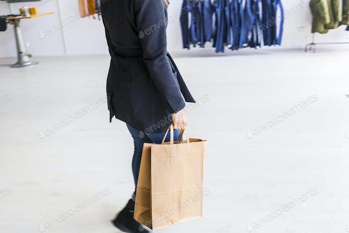 Niedriger Abschnitt der Frau trägt Einkaufstasche in der Fabrik