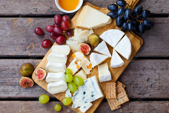 Cheese and fruits assortment on cutting board on wooden background. Top view.