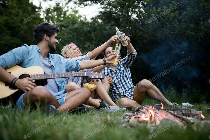 Group of friends camping.They are sitting around camp fire, playing guitar