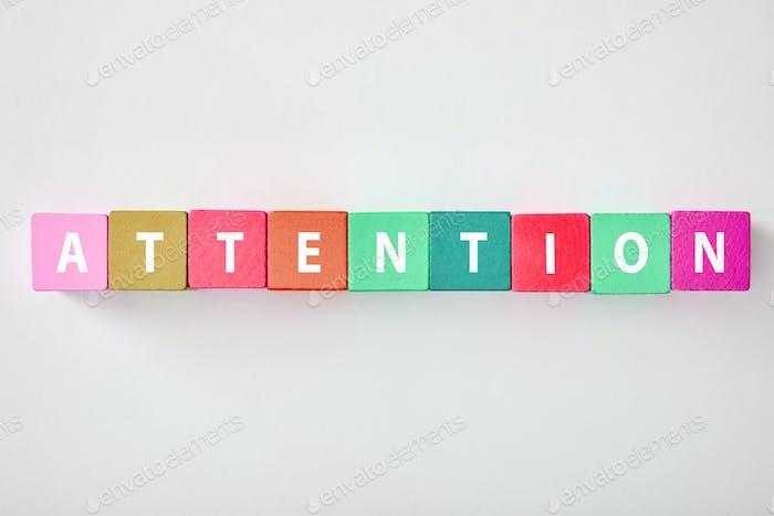 Draufsicht auf Aufmerksamkeitsbeschriftung aus bunten Würfeln auf grauem Hintergrund