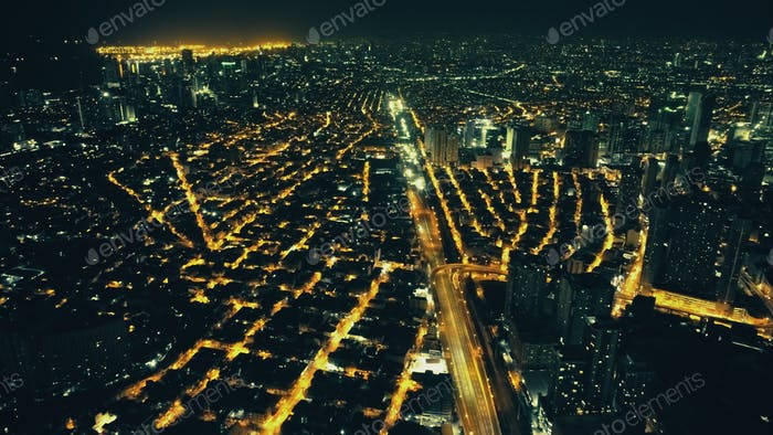 Illuminate streets of Manila downtown cityscape at night. Aerial traffic city route. Urban transport