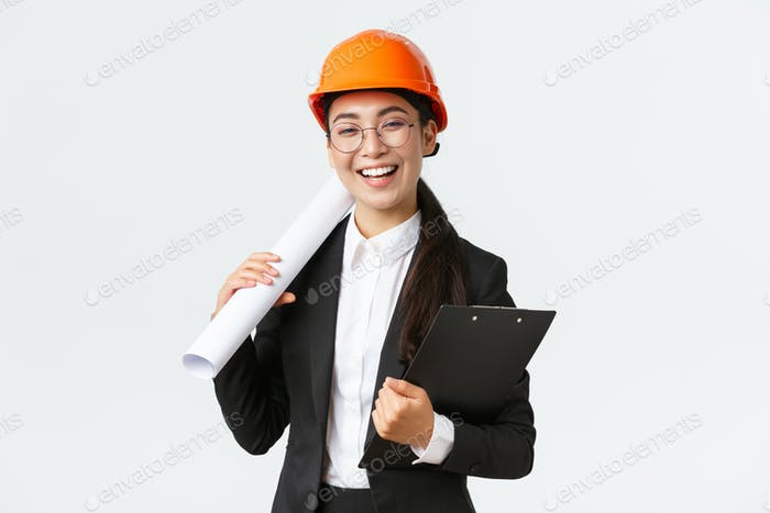 Professional happy asian female architect, construction engineer in helmet and business suit holding