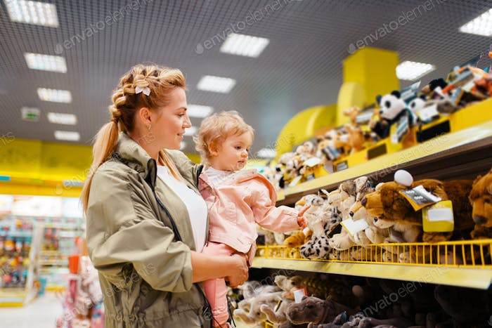Mother with her girl choosing toys in kids store