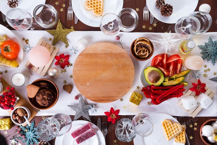 Christmas table setting with food on a plate and decoration on dark wooden table, flat lay