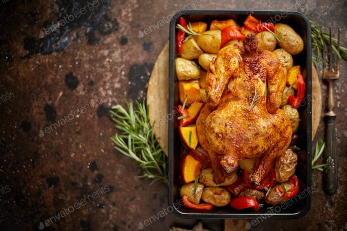Whole roasted chicken or turkey with pumpkin, potatoes, red pepper and rosemary