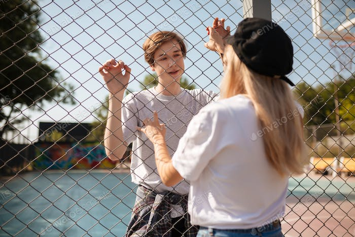 Guy standing on basketball court dreamily looking at pretty girl through mesh fence