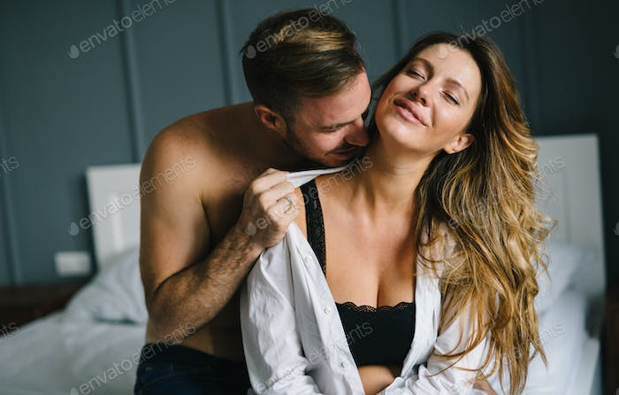 Attractive couple sharing intimate moments in bedroom