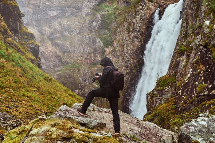 Nature photographer tourist with camera shoots while standing on the mountain against a waterfall.
