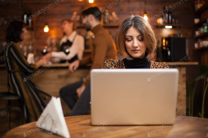 Blonde businesswoman working on her laptop in a coffee shop
