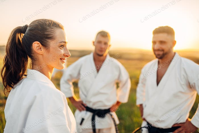 Two male and one female karate fighters in field