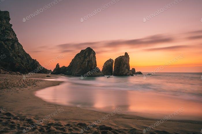 Ursa Strand in der Nähe von Cape Roca an der Atlantikküste in Portugal. Sandstrand mit Meerestapeln am Abend