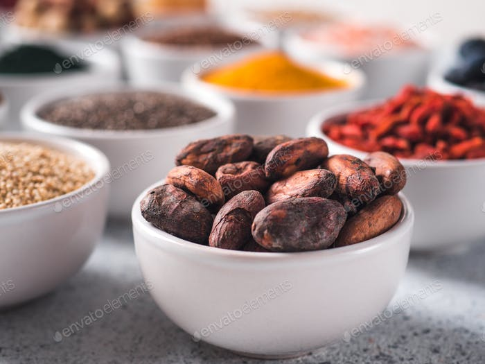 Rohe Kakaobohne in kleinen weißen Schüssel und andere Superfoods