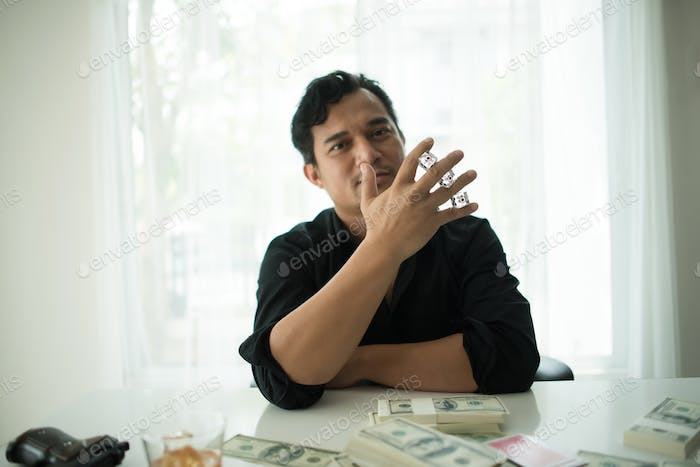 Businessman sitting in a business center bar gambling and money on the table.